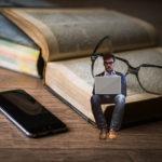 パソコンや本で知識をつける男性