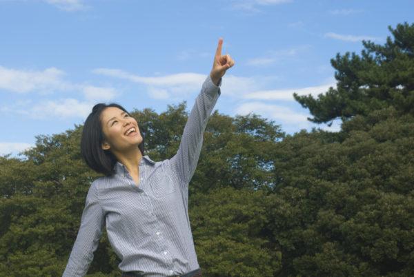 空を指さす女性